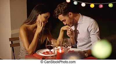 Romantic chivalrous young man kissing the hand of his...