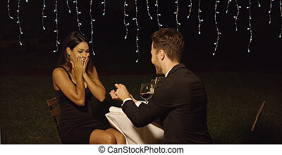 Shocked young woman receiving a marriage proposal - Shocked...