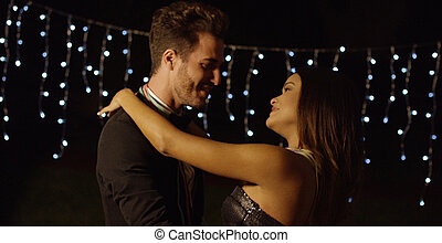 Elegant young couple dancing at night against twinkling...