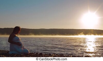 Pregnant Sits On The Lake In The Early Morning And Watch The...