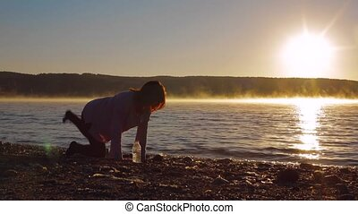 Pregnant Woman At Dawn Doing Exercise. - A woman stands on...