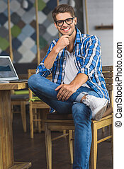 successful nerd sitting on a chair and smiling - nerd...