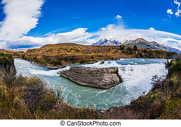 Emerald Paine river forms a cascading waterfalls. Torres del...