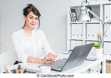 Close-up portrait of a businesswoman at her workplace working with pc, looking in camera, wearing office suit.