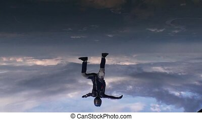 Skydiver freestyle falling in evening cloudy sky Speed...