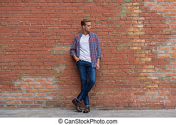 Handsome guy standing near brick wall - Casual city style...