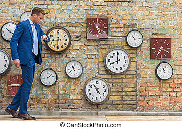 Man in suit standing near wall with clocks
