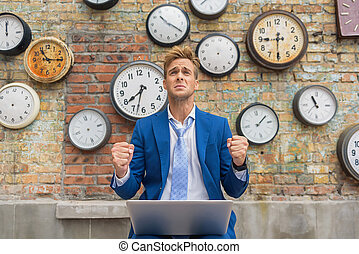 Man in suit sitting near wall with clocks