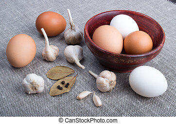 Raw eggs and garlic and spices on the kitchen table on the...