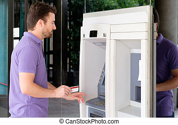 Man using his credit card in an atm for cash withdrawal