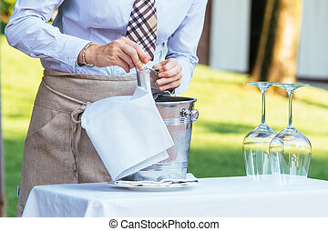 Waiter opening a champagne bottle for a toast