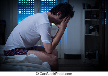 Sad and lonely man seated on his bed