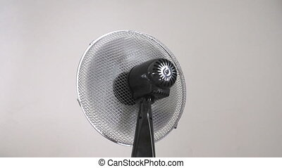 Fan on gray background loop - Oscillating fan spinning and...