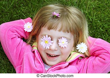 little girl laying grass daisiy flowers in eyes - little...