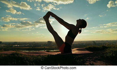 Woman doing yoga in floating boat pose in the park at sunset