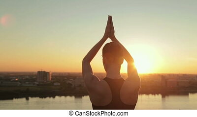 Sporty woman practicing yoga in the park at sunset - sun...