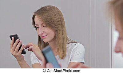 Woman using smartphone sitting in front of mirror - Pretty...