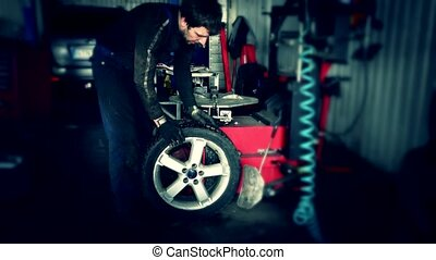 mechanic using tire mounting tool machine. Car repair...