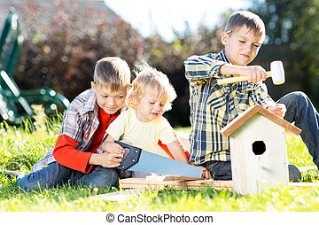 Kids making birdhouse together sitting on the grass Oldest...