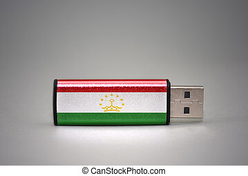usb flash drive with the national flag of tajikistan on gray...