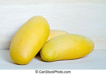 Mango on wooden background (Also known as horse mango, Mangifera foetida, Anacardiaceae, Mangifera, M. indica)