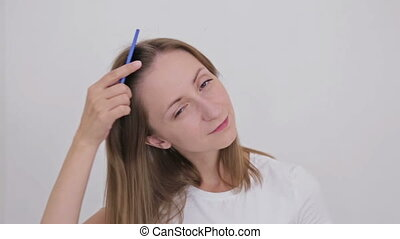 Young pretty woman combing her hair and looking at camera....
