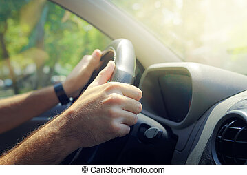 Male hands holding car steering wheel the right way for safe...