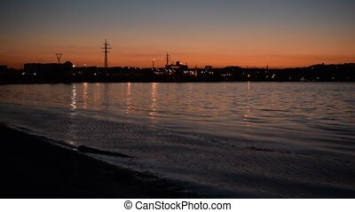 Time lapse of nightfall in the city near shore with city...