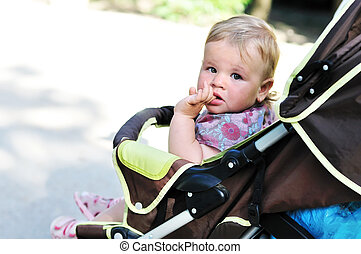 baby girl in the pram licking finger
