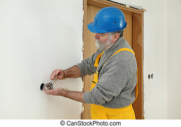 Electrician at construction site install electrical plug -...