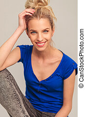 laughing young blonde woman sitting and holding her hand on...