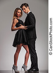 sexy couple in elegant clothes standing embraced and looking...