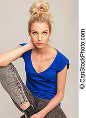 portrait of a seated blonde woman in jeans