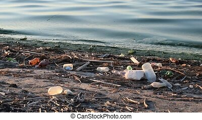 Trash on shore with dirty water - Large amount of trash on...
