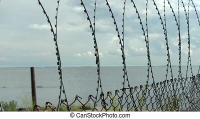 Sea behind barbed wire fences - seascape View from the...