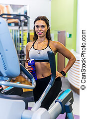 Fit woman doing exercise on a elliptical trainer - Fit woman...