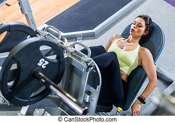 Top view of a fit young woman doing leg press in the gym.