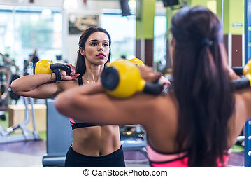 Fitness woman doing exercise with a kettle bell.
