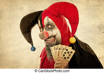 Evil Fool holding playing cards, vintage filtered, concept...