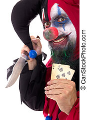 Evil clown holding a Knife and playing cards, isolated on...