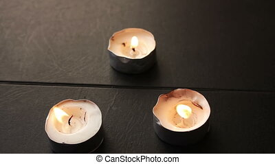 Three round candles on a black background.Full HD 1920 x...
