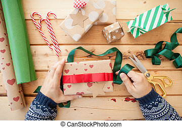 Wrapping christmas presents on rustic wooden background