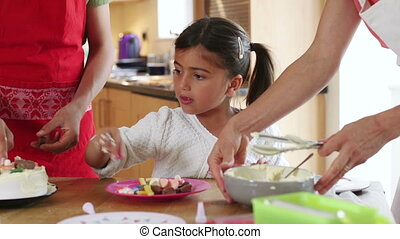 Decorating a Cake - Little girl decorating a cake at home...