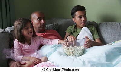 Family Film time - Father at home with his children. They...