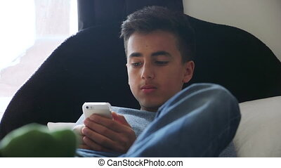 Teenager using Smartphone - Teenage boy lying on his bed at...