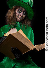 funny goblin girl is reading from a book, concept fairytales...