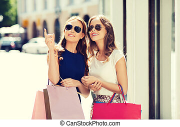 happy women with shopping bags in city
