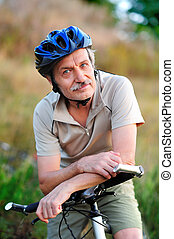 closeup portrait of a senior man cyclist with his bicycle in...