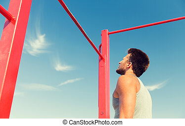 young man exercising on horizontal bar outdoors - fitness,...
