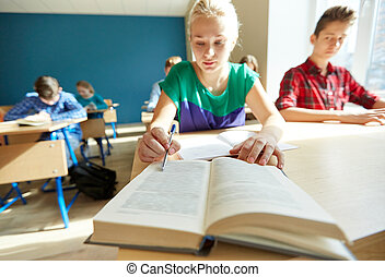 group of students with books writing school test -...
